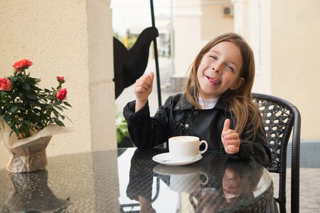 Little prankster schoolchild enjoys a coffee drink. She is pleased and happy. Milk foam on his face as the mustache. Incredibly delicious
