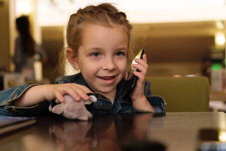Charmante petite fille communique à l'aide d'un téléphone portable. Tarif enfant. Être en contact. Appeler des proches