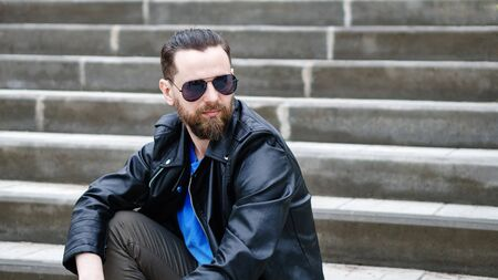 Fashion portrait of young bearded man. Handsome hipster guy posing in sunglasses Фото со стока