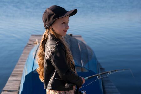 Child is fishing from wooden pier on a lake. Cute little schoolgirl have fun fishing. Leisure during  sunny day. Relaxing outdoors