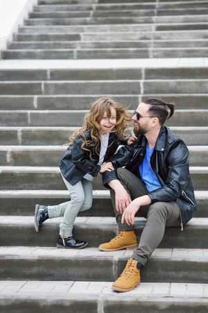 Fashionable stylish family portrait for a walk. Dad and daughter posing on the city stairs. Excursion. Travel and tourism concept. Time together. Family look. Urban casual outfit.