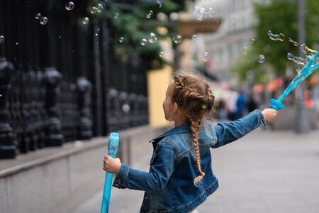 Adorable little girl having fun outdoors, blowing bubbles in city street. Carefree time. Happiness, fun and childhood concept. Stok Fotoğraf