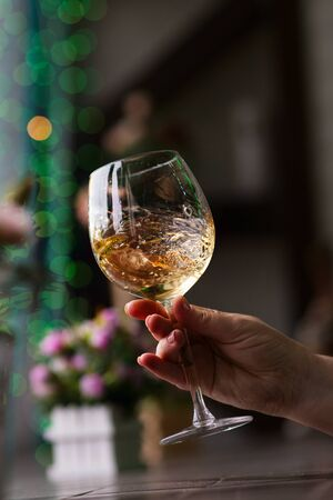 Hand sommelier holding glass of white wine. Swirling wine glass in wine tastings White wine concept. Wine tour. Vertical, cold toning