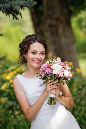 Emotional portrait of a happy bride in fashion wedding dress on natural background. Newlywed with a wedding bouquet in her hand laughs happily after the wedding ceremony. Wedding day.