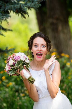 Emotional portrait of joyful bride in wedding dress on natural background. Newlywed with wedding bouquet in her hand laughs happily after wedding ceremony. Wedding day. Surprise. Bridal fashion Reklamní fotografie