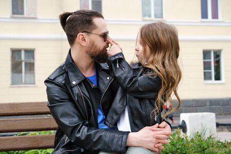 Famiglia alla moda alla moda per una passeggiata. Felicità di essere un genitore. La piccola figlia affascinante è seduta sulle ginocchia di suo padre. Tempo di scherzo. Conversazione riservata. Aspetto familiare. Archivio Fotografico