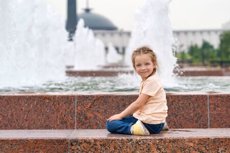 Cute little mischievous girl plays at the fountain. Time of prank. Urban casual outfit. Carefree. Happiness, fun and childhood concept.