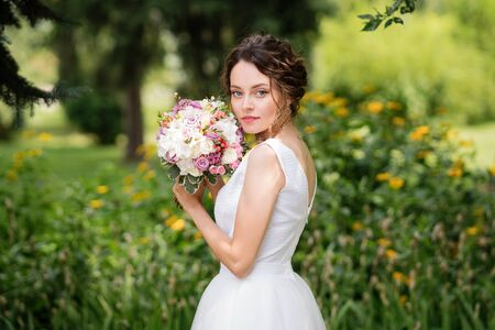 Beautiful bride in fashion wedding dress on natural background. The stunning young bride is incredibly happy. Wedding day. A beautiful bride portrait in the park.