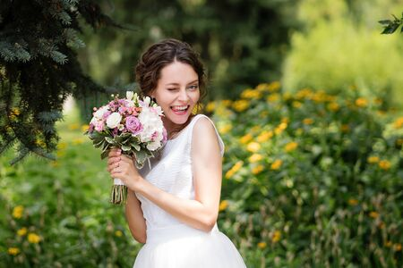 Young beautiful stylish wife. Bride bouquet. Graceful hairstyle, beauty make-up, white dress. Funny face expression, emotion, smiling, happy, surprise. Bridal fashion, spring trend. Wedding day. Reklamní fotografie