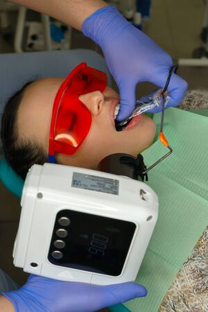 Dentist makes x-ray in a girl patient. Close-up shot. Health care concept. Dental medical procedures Stock Photo - 129691629