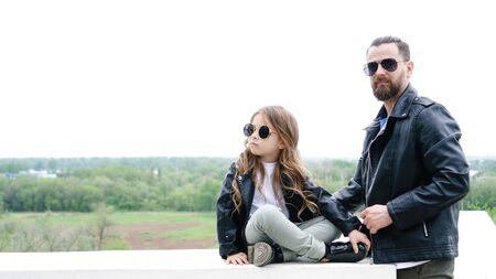 Famiglia alla moda alla moda per una passeggiata. Affascinante scolaretta e il suo bel giovane papà trascorrono del tempo insieme all'aperto. Aspetto familiare. Abito casual urbano. Toni smorzati Archivio Fotografico