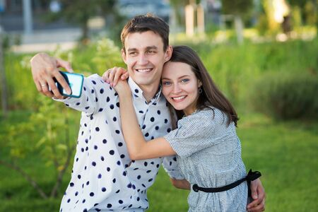 Beautiful couple in love dating outdoors and smiling. Girl persuades her boyfriend to take a picture of herself together. Selfie. Keep a moment in mind. Happy time together