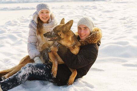 Joyful teens spend time together with lovely pet German Shepherd Dog on a walk in the winter park on a sunny day. Having fun playing in snow outdoors. Time for cheery. Happy family. Playful mood Banco de Imagens