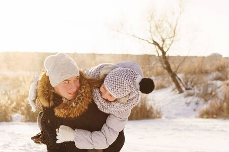 Joyful brother and sister spend time together on a walk in the winter park on a sunny day. Having fun playing in snow outdoors. Winter best time for cheery