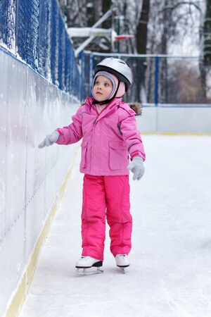 Beautiful girl having fun in winter park, balancing while skating at ice rink. Enjoying nature, winter time. Baby takes her first steps in figure skating