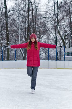 Beautiful girl having fun in winter park, balancing while skating at ice rink. Enjoying nature, winter time. Woman takes her first steps in figure skating