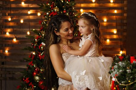 Family celebrates Christmas. Happy mother with daughter in magic night. Sharing Christmas presents on the main plan. Merry Christmas and Happy Holidays. Tenderness, care and mutual understanding