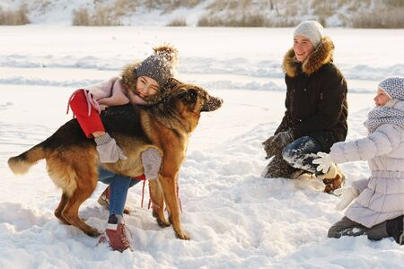 Joyful teens spend time together with lovely pet German Shepherd Dog on a walk in the winter park on a sunny day. Having fun playing in snow outdoors. Time for cheery. Happy family. Playful mood Banque d'images