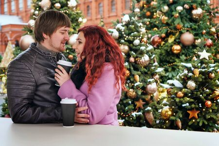 Couple drinking hot beverage during walk by Christmas market. Holidays, winter, christmas and people concept - happy couple in warm clothes outdoors. Got together at a christmas tale Stock fotó