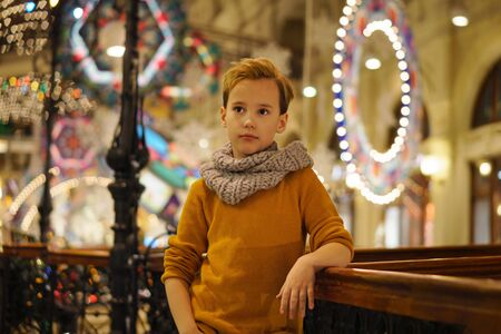Dressed in stylish modern casual wear, young schoolboy posing in shopping center decorated for Christmas. Garlands and christmas lights on background in defocus.