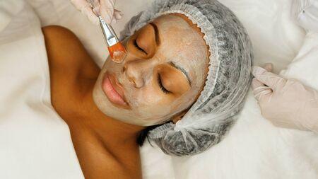 Auftragen einer Kosmetikmaske auf das Gesicht einer jungen Afroamerikanerin. Verfahren zur Verjüngung der Gesichtshaut. Beauty, Spa, Kosmetik und Jugendschutz. Wellness-Entspannungskonzept.