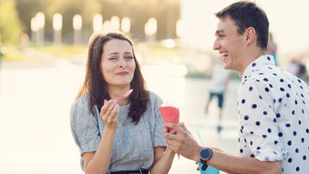 Happy young couple in love having fun and walk on the summer day. Girlfriend and boyfriend spend time together in park. Lovers enjoying themselves prank. Street fast food. Ice-cream and milkshake Banco de Imagens