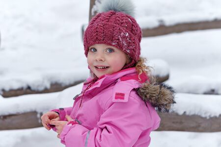 Closeup portrait, charming sweet, stylishly dressed child. Fashionable girl on a walk in winter. Relaxing outdoors. Ampaigns and adventures. Lifestyle concept.
