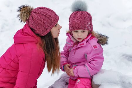 Confidential conversation, mother and daughter come to an agreement and mutual understanding during joint winter walk in park. Happiness to be parent. Family look. Фото со стока