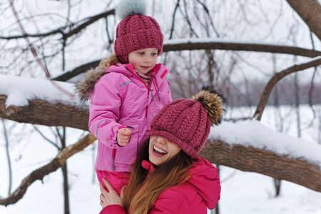 Time of mischief and pranks. Family winter fun. Fashionable stylish family for a walk. Mom and daughter in the park. Happiness to be a parent. Family look. Lifestyle concept.