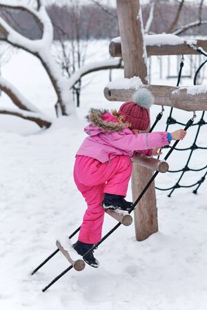 Active leisure on the playground of a charming sweet, stylishly dressed child. Fashionable girl on a walk in winter. Sport, health. In a healthy body healthy mind