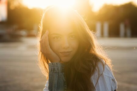 Back light portrait of a happy single teen girl breathing fresh air in a city street during a sunny day at sunset in a park with a warm yellow light and urban background. Summertime. Lifestyle.