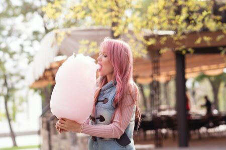 Adorable young woman with long pink hair eats and poses with sugar pink candy cotton. Concept happy times. Carefree girl. Good mood