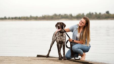 Best friends young woman and German Shorthaired Pointer sitting on by the river. Girl stroking her dog.Concepts of friendship, pets, togetherness Stock Photo