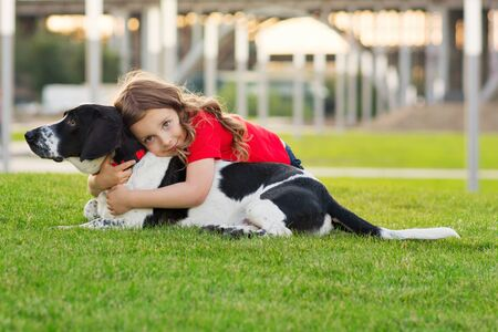 Beautiful young girl is hugging her pet. Cute photo of dog and its owner relaxing on the grass. Faithful friends of human. Concepts of friendship, leasure, pate care, togetherness. Domestic animal.