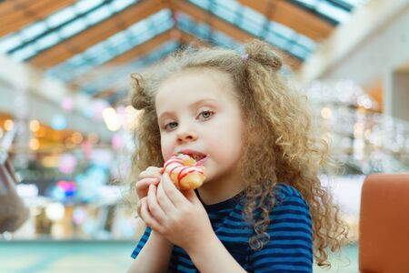 Cute little curly girl chews donut in mall. Baby is enjoying snack. Fast food. Food court