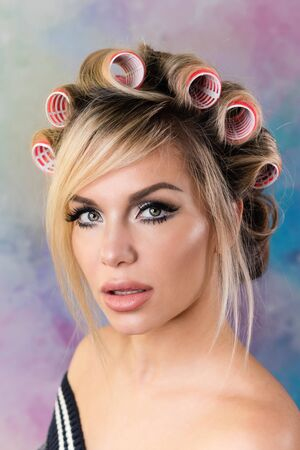 Close up portrait of cheerful blonde pin up girl. Beautiful girl with curlers smiles sweetly and looks at you. Presenting your product. Expressive facial expressions. Colorful background