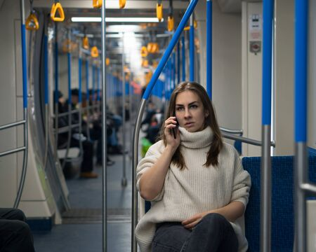 Girl speaks on cell phone inside an empty subway train. A beautiful woman tourist of appearance sits in subway car. Portrait of female passenger using mobile phone. Stock Photo