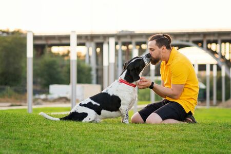 Handsome hipster man on a walk with a dog. Friendship loving bond between owner and pet hunting dog. Faithful friends of human. Concepts of companionship, pretty leasure, togetherness 写真素材