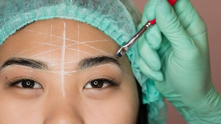 Eyebrow tinting and dyeing. The master paints eyebrows with henna to a beautiful girl, paints with a brush in the salon of a beautician-makeup artist. Brow architecture.