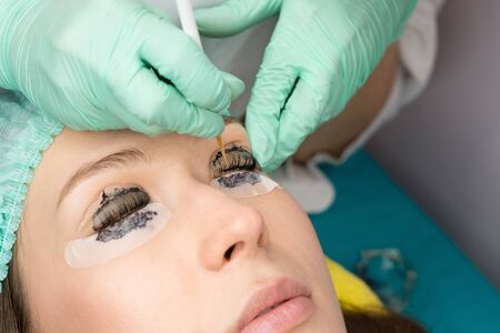 Beauty treatment. Cosmetologist puts black paint on the lashes. Laminating eyelashes. Closeup eyes.