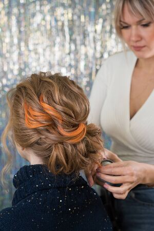 Hairdressing services. Creation of evening hairstyles fashionable stylish womens hairstyles. Hair styling process. Hairtician fixes hair with hair spray. Back view. Elegant colored hairstyle. Trendy
