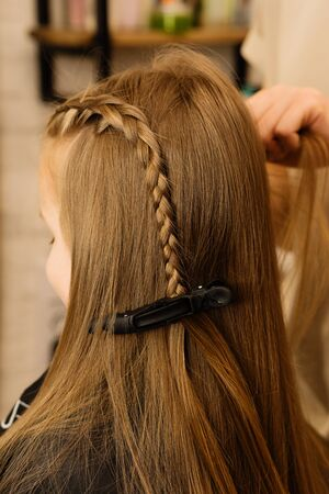 Process of braiding the master weaves braids on her head blond little girl in beauty salon close up. Professional hair care and creating hairstyles.