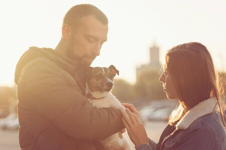 Romantic happy couple in love enjoying their time with pets. Loving couple having fun with dog at the walk. Concept people, animals and lifestyle. Sunset warm