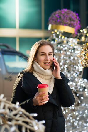 Portrait busy modern pretty woman talking on smartphone. Attractive business lady holding takeaway coffee, using phone. Business woman on background modern business center. Bokeh christmas lights
