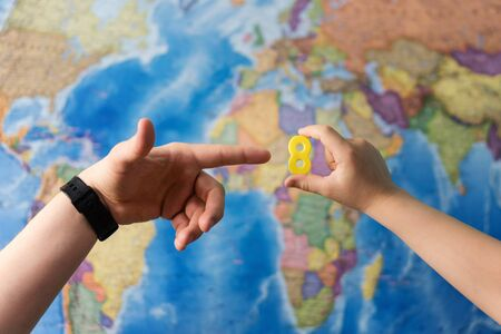 Adult and child hands holding numbers plastic toy on the world political map background. Travel planning explore destination concept. Family holidays and time together. Quarantine over, borders open Фото со стока