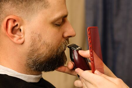 Barber trimming beard of male customer with electric razor at barbershop. Man with beard and moustache getting stylish trendy hair shaving, with hair clipper and comb. Close up. Banque d'images