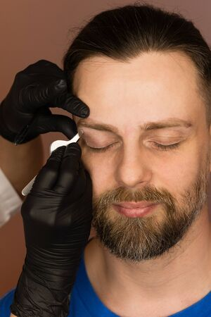 Professional barber doing threading procedure and correcting shape of eyebrows to young male client with tweezer in barber shop. Barber at work. Brow care concept. Plucking brows Stock Photo