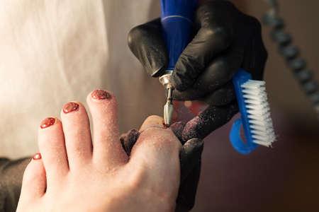 Pedicure. Gel polishing. Translucent base application. Process pedicure close up in a fashionable spa salon, unrecognizable people