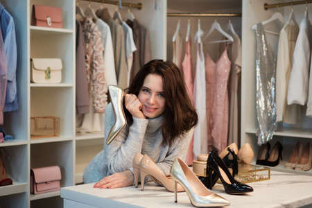 Young pensive beautiful girl choosing shoes from large wardrobe closet with stylish clothes, shoes and home stuff. Nothing to wear concept. Choosing shoes for special occasion. Banco de Imagens