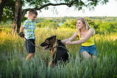 Young cheerful family is walking with his dog a German shepherd in the meadow. Mom and son spend time together and have fun in nature with a pet.